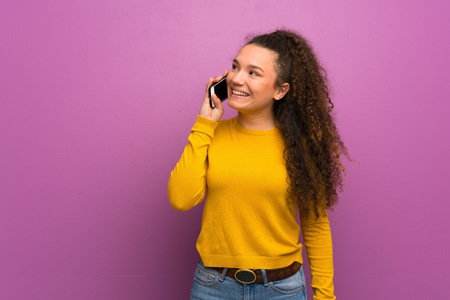 Teenager girl over purple wall keeping a conversation with the mobile phone Zdjęcie Seryjne