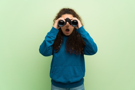 Teenager girl over green wall and looking in the distance with binoculars