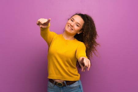 Teenager girl over purple wall points finger at you while smiling