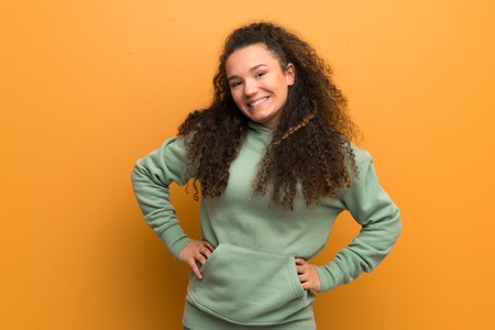 Teenager girl over ocher wall posing with arms at hip and smiling