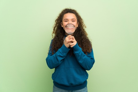 Teenager girl over green wall taking a magnifying glass and showing teeth through it