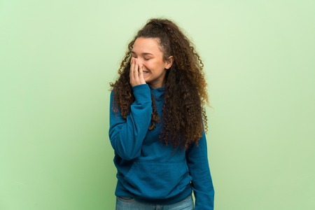 Teenager girl over green wall posing with arms at hip and laughing