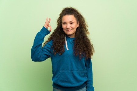 Teenager girl over green wall showing an ok sign with fingers