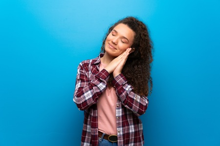 Teenager girl over blue wall making sleep gesture in dorable expression