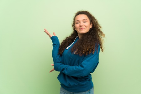 Teenager girl over green wall extending hands to the side for inviting to come Zdjęcie Seryjne