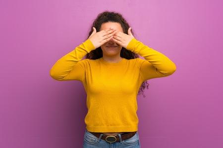 Chica adolescente sobre la pared púrpura que cubre los ojos con las manos