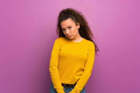 Teenager girl over purple wall with sad and depressed expression Zdjęcie Seryjne
