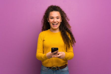 Teenager girl over purple wall sending a message with the mobile Zdjęcie Seryjne