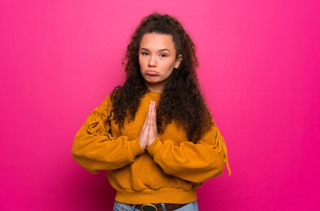 Teenager girl over pink wall keeps palm together. Person asks for something
