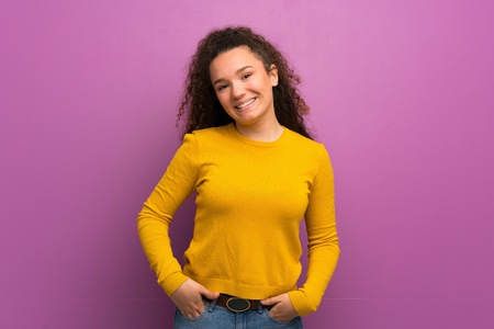 Teenager girl over purple wall laughing