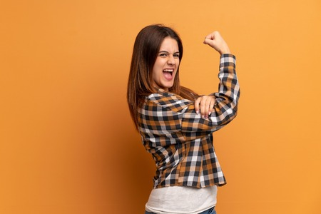 Young woman over brown wall doing strong gesture Archivio Fotografico