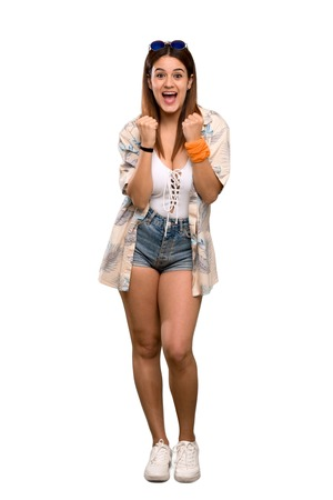 Full-length shot of Young woman in bikini in summer holidays celebrating a victory in winner position over isolated white background Stockfoto
