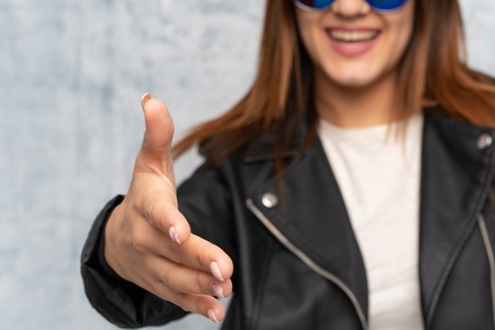 Young woman over textured wall handshaking after good deal Stock Photo