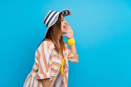 Jeune femme en bikini en vacances d'été criant avec la bouche grande ouverte sur le côté
