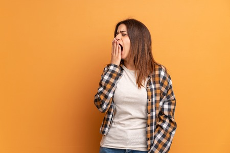 Young woman over brown wall yawning and covering wide open mouth with hand