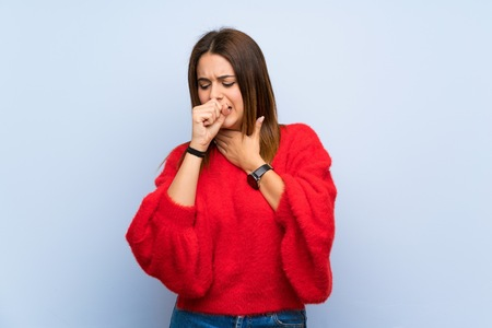 Young woman over isolated blue wall is suffering with cough and feeling bad