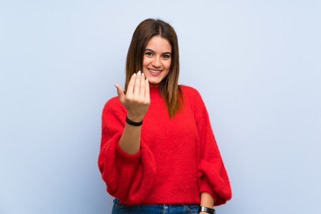 Young woman over isolated blue wall inviting to come with hand. Happy that you came