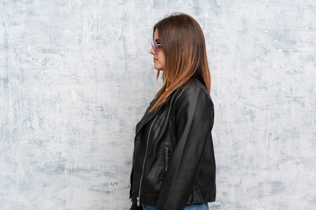 Young woman over textured wall keeping arms crossed and looking side
