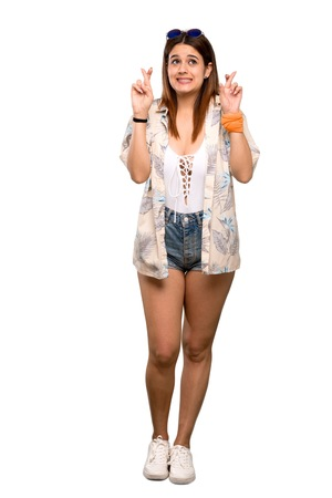 Full-length shot of Young woman in bikini in summer holidays with fingers crossing and wishing the best over isolated white background
