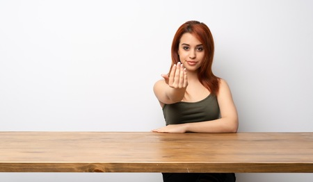 Young redhead woman at desk inviting to come with hand. Happy that you came