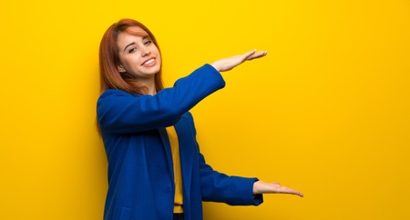 Young redhead woman with trench coat holding copyspace to insert an ad Foto de archivo