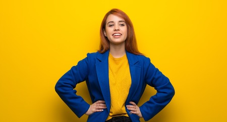 Young redhead woman with trench coat posing with arms at hip and smiling