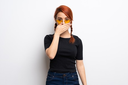 Young redhead woman over white wall covering mouth with hands for saying something inappropriate