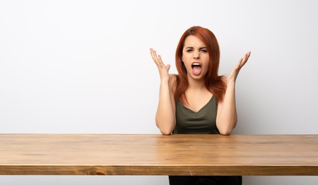 Young redhead woman at desk frustrated by a bad situation