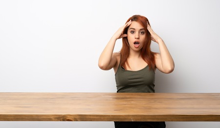 Young redhead woman at desk with surprise expression