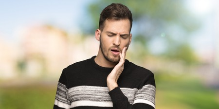 Handsome man with toothache at outdoors