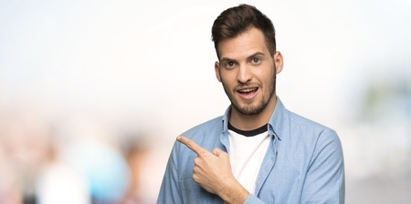 Handsome man pointing to the side to present a product at outdoors