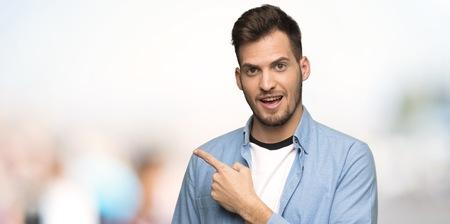 Przystojny mężczyzna wskazuje na bok, aby zaprezentować produkt na zewnątrz