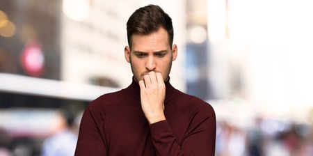 Man with turtleneck sweater having doubts in the city