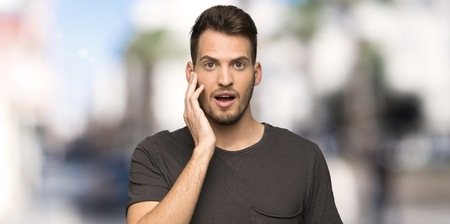 Man with black shirt with surprise and shocked facial expression at outdoors