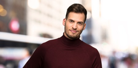 Man with turtleneck sweater posing with arms at hip and smiling in the city
