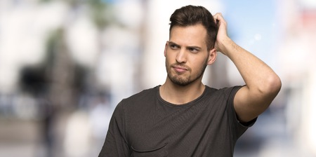 Man with black shirt having doubts while scratching head at outdoors