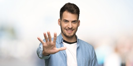 Handsome man counting five with fingers at outdoors
