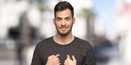 Man with black shirt with surprise facial expression at outdoors Imagens