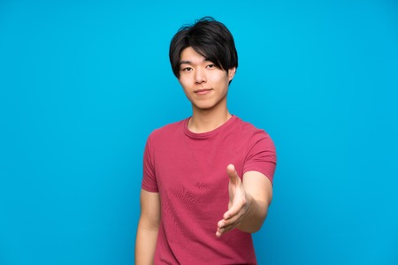 Asian man with red shirt over isolated blue wall handshaking after good deal Reklamní fotografie