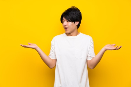 Asian man over isolated yellow wall holding copyspace with two hands