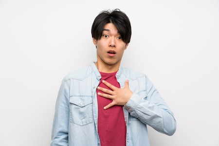 Asian man on isolated white background surprised and shocked while looking right Фото со стока
