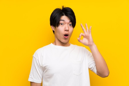Asian man over isolated yellow wall surprised and showing ok sign