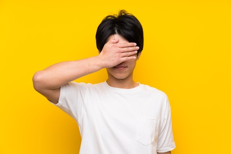 Asian man over isolated yellow wall covering eyes by hands. Do not want to see something Stock Photo