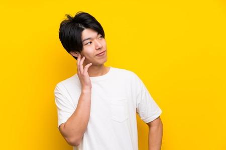 Homme asiatique sur un mur jaune isolé pensant à une idée