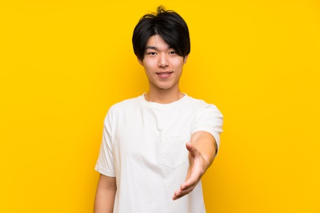 Asian man over isolated yellow wall shaking hands for closing a good deal
