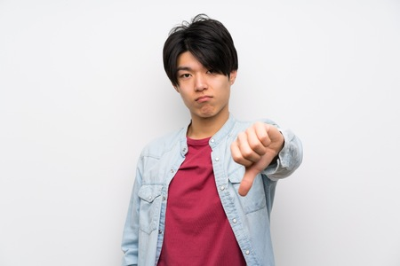 Asian man on isolated white background showing thumb down with negative expression