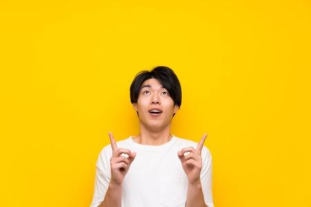 Uomo asiatico sopra il muro giallo isolato sorpreso e rivolto verso l'alto Archivio Fotografico