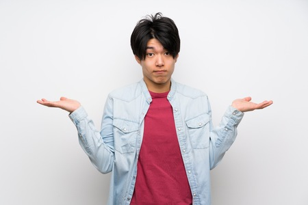 Asian man on isolated white background having doubts while raising hands