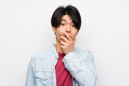 Asian man on isolated white background surprised and shocked while looking right