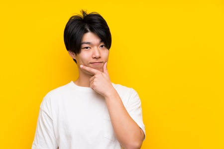 Asian man over isolated yellow wall thinking